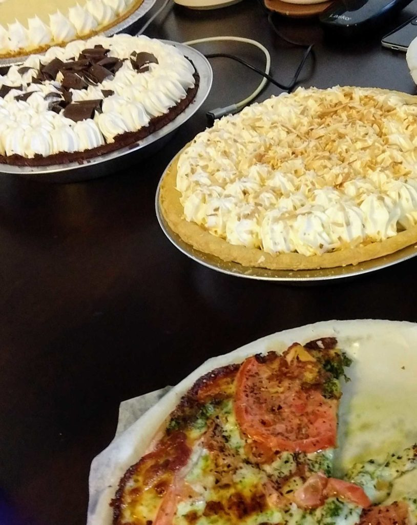Pi Day at CourseStorm - table with pizza, coconut cream, chocolate cream, and key lime pies